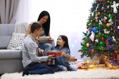 Happy family with gifts in the decorated Christmas room