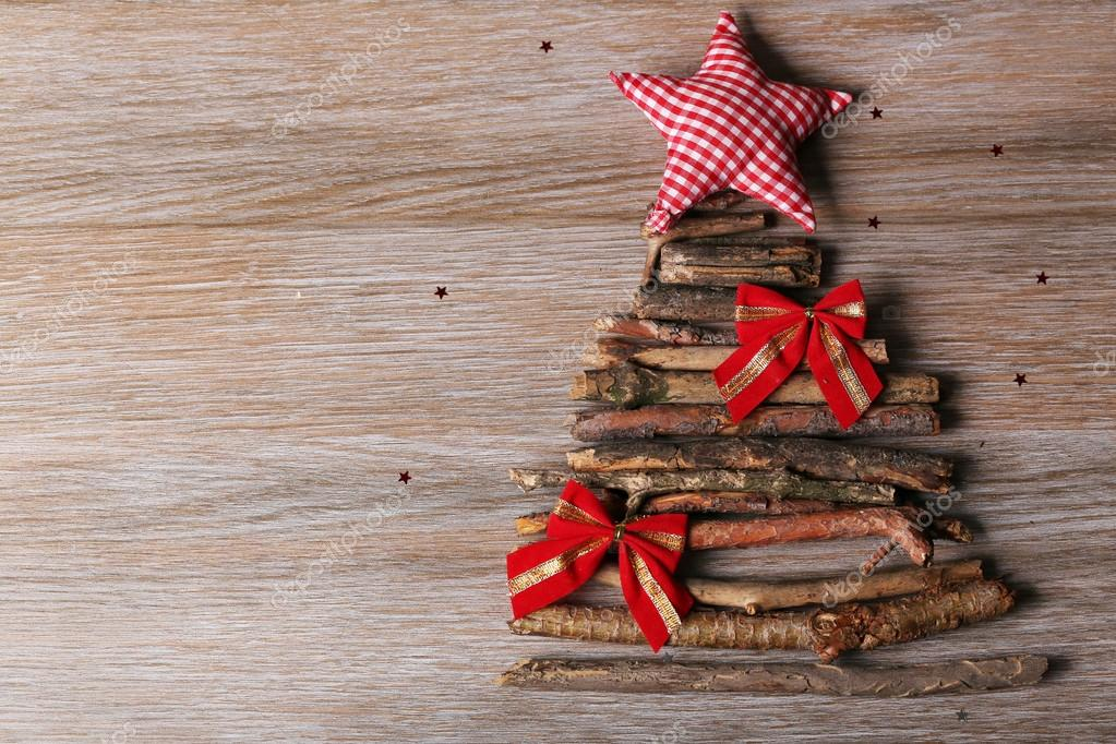 Christmas tree made of wooden branches on wooden table top view