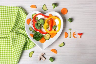 Useful cut vegetables on a plate in the form of heart on wooden table top view