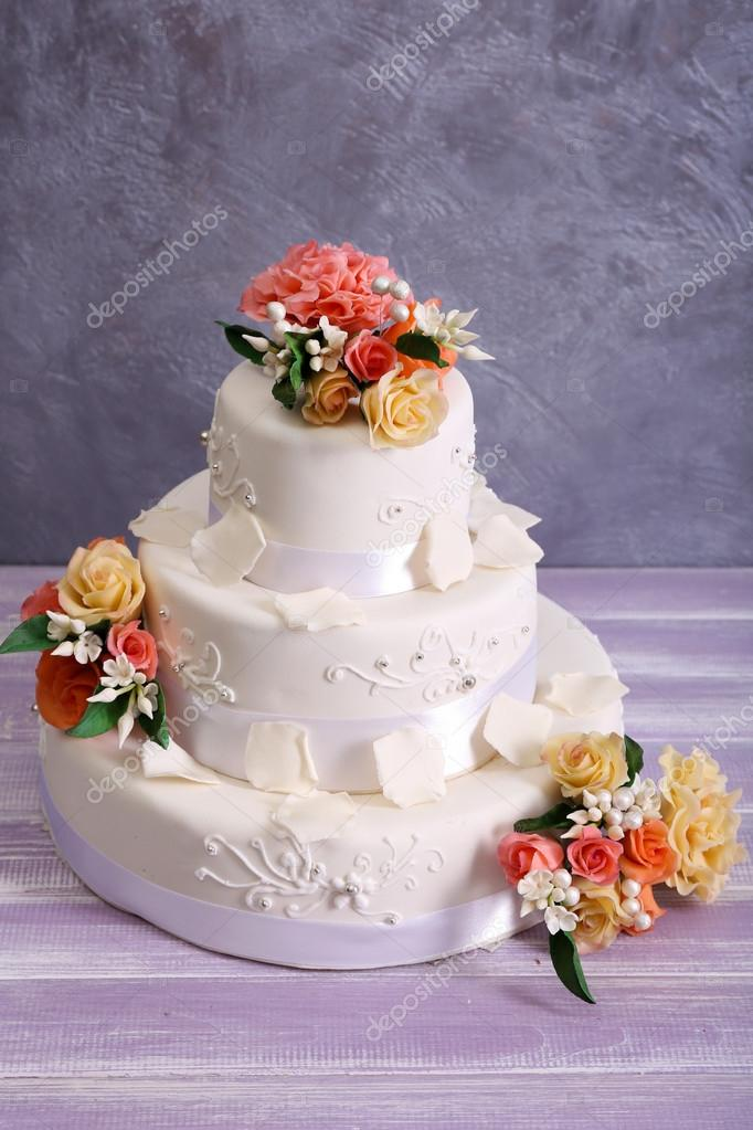 White Wedding Cake Decorated With Flowers On Wooden Table Against