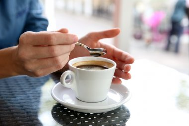 Cup of coffee with hands and spoon
