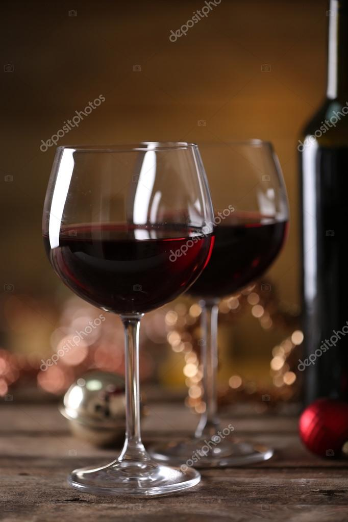 red wine and christmas ornaments on wooden table on wooden background stock photo