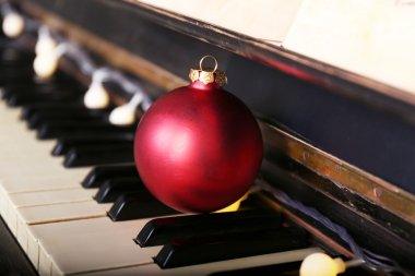 Piano keys decorated with decoration lights and red ball, close up