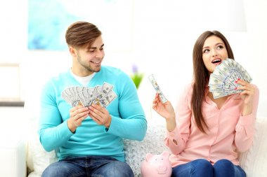 Happy couple sitting at home and counting money from the pig money box