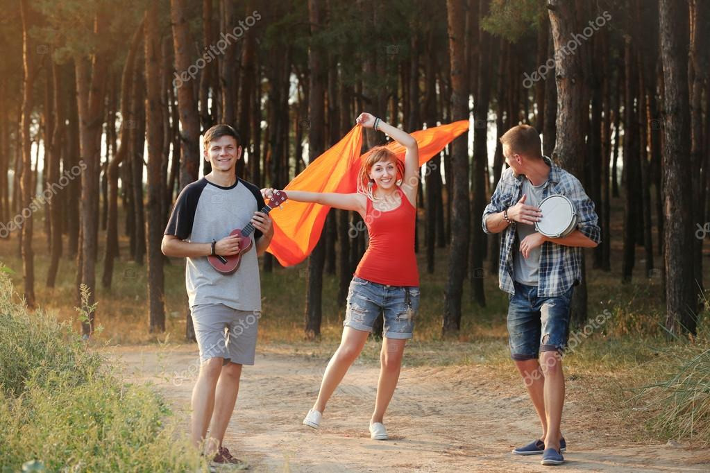 Trio of smiling friends with musical instruments relaxing in the forest outdoors