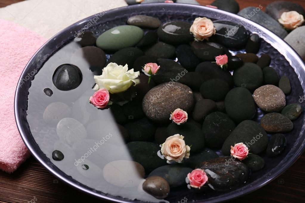 Spa composition of flowers and stones in water, close-up