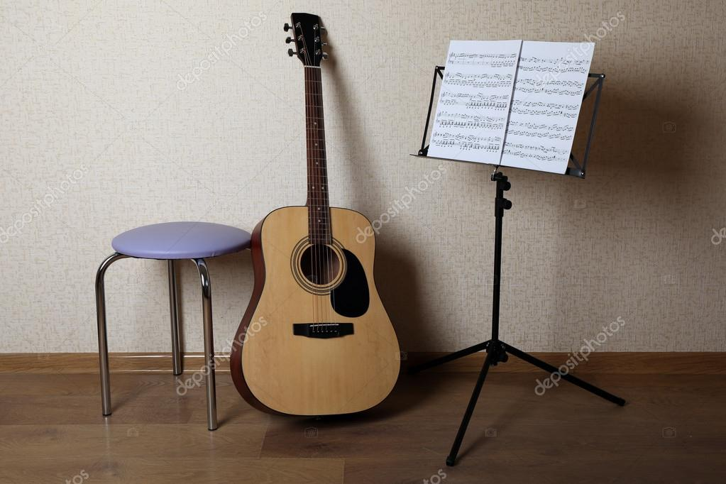Chitarra acustica appoggiata sulla parete con sgabello e titolare di