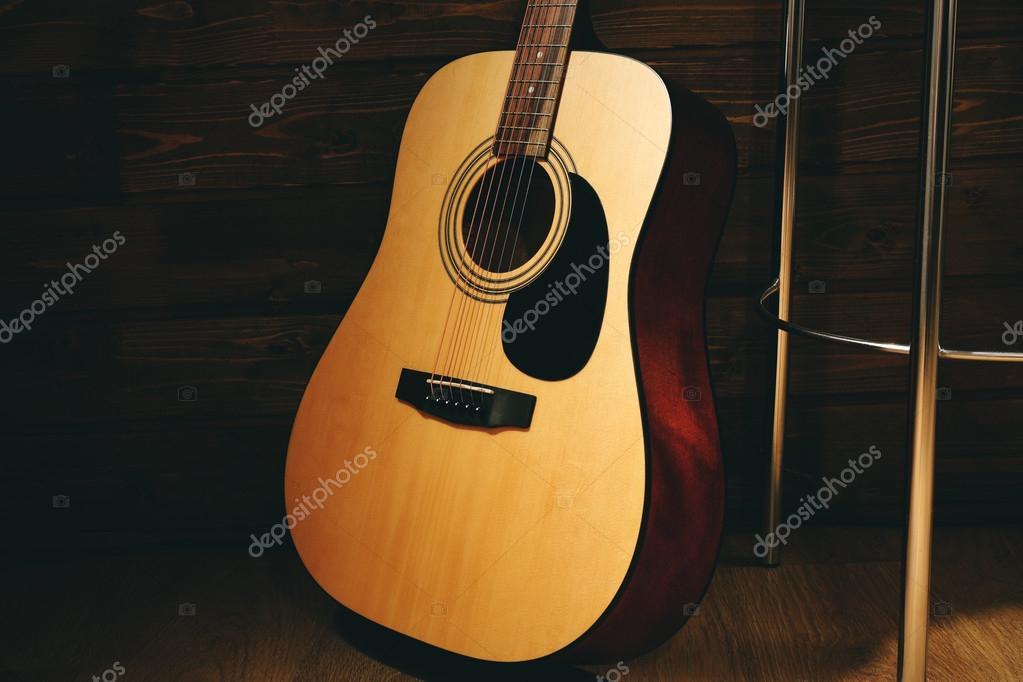 Chitarra acustica appoggiata sulla parete di legno con sgabello bar