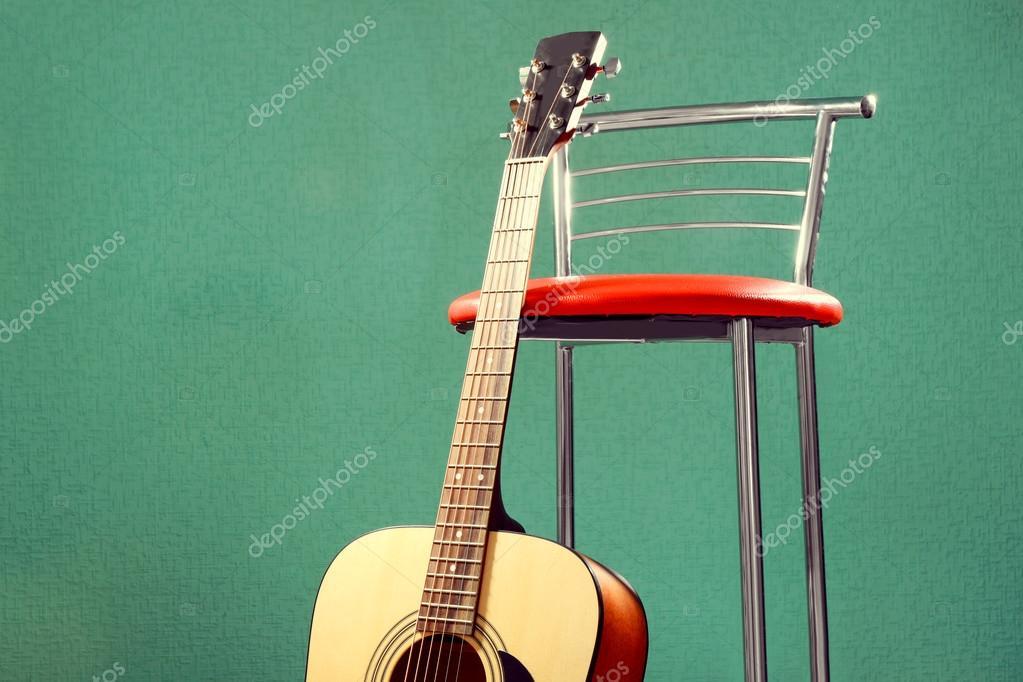 Chitarra con sgabello al piano su uno sfondo blu in studio primi
