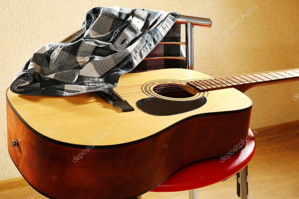 Chitarra acustica su sgabello rosso in studio primi piani u2014 foto