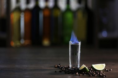 Burning cocktail with lime and coffee beans on table in a bar
