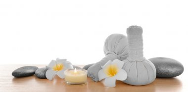 Massage bags with plumeria and candle, isolated on white