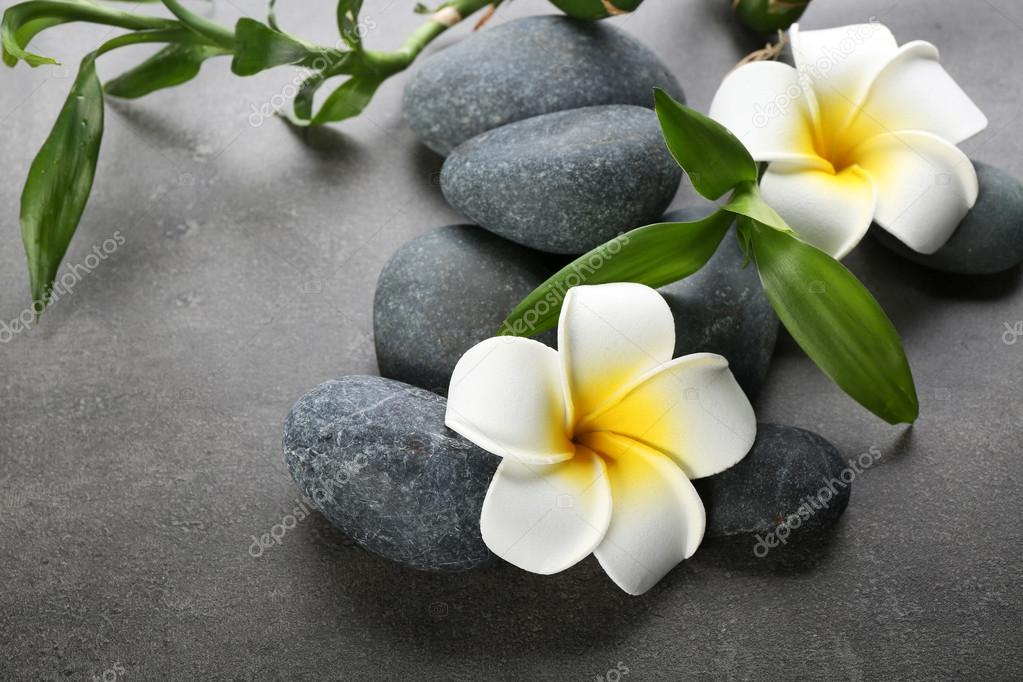 Hot spa stones with flowers and bamboo on grey background, close-up