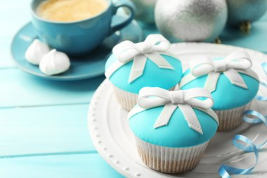 Tasty cupcakes with bow, coffee cup and Christmas toys on color wooden background