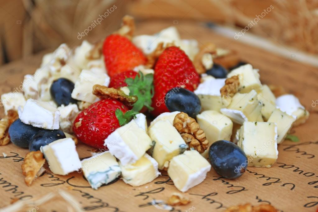 Cheese and berries on paper