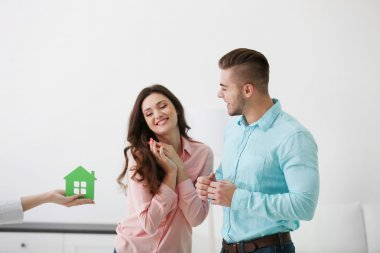 realtor giving model of house to couple