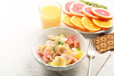 Fruit salad on wooden background. Healthy eating concept.