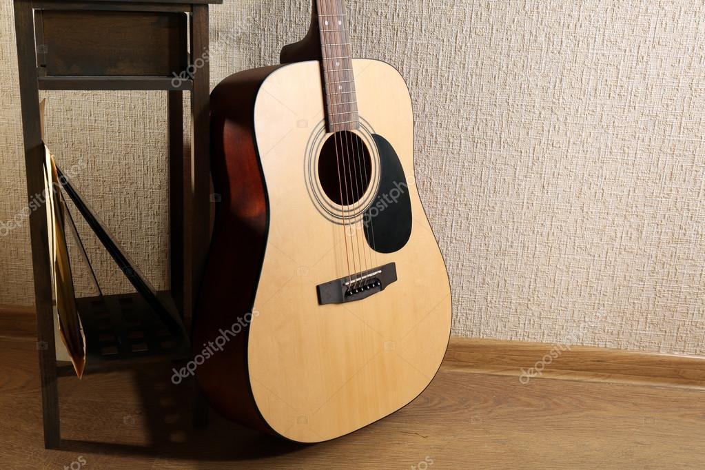 Chitarra acustica appoggiata sulla parete con sgabello e cuffie su