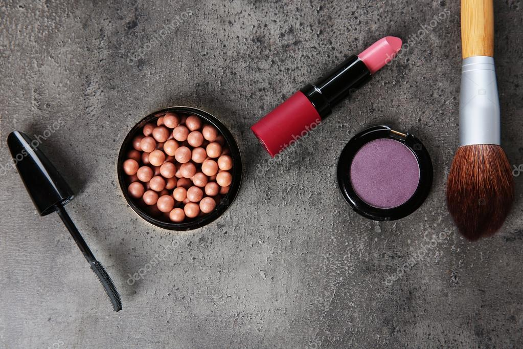Makeup Brushes And Cosmetics On Grey Background Stock Photo