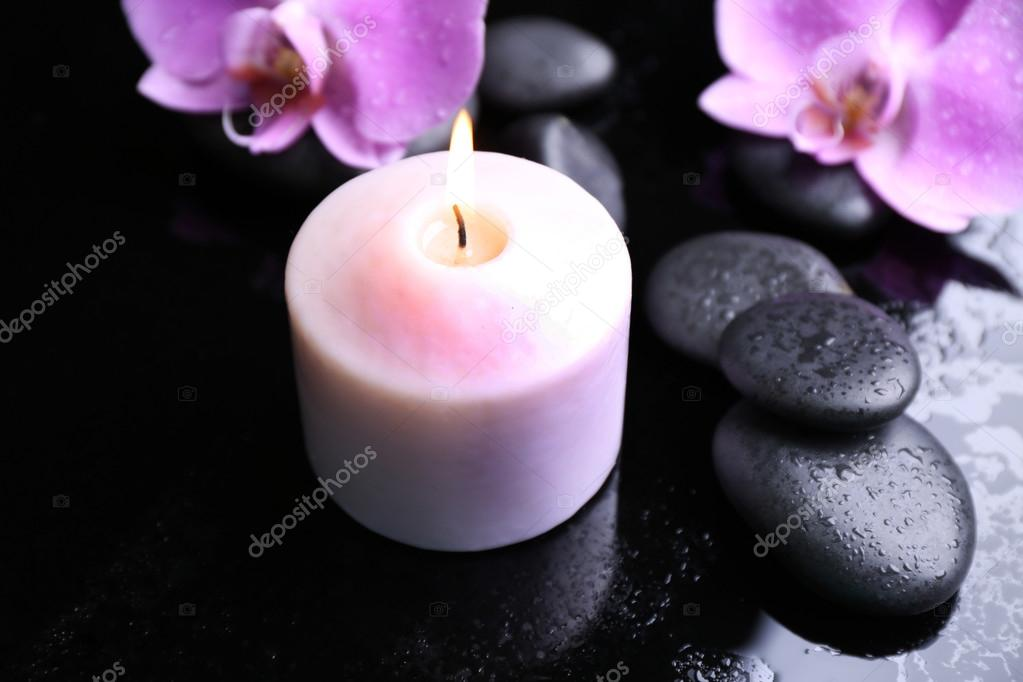 Composition of orchids, pebbles and candle