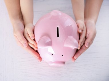 Parent and child hold piggy bank