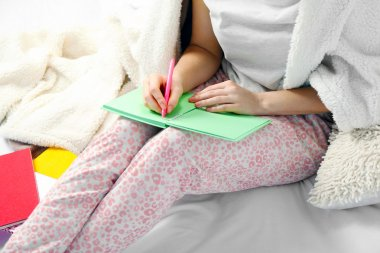 Woman in pajamas writing diary