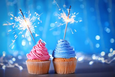 Two cupcakes with sparklers on a glitter background