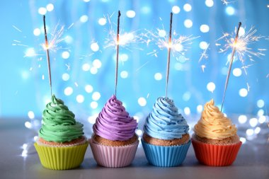 Varicolored cupcakes icing with sparklers in a row on a glitter background