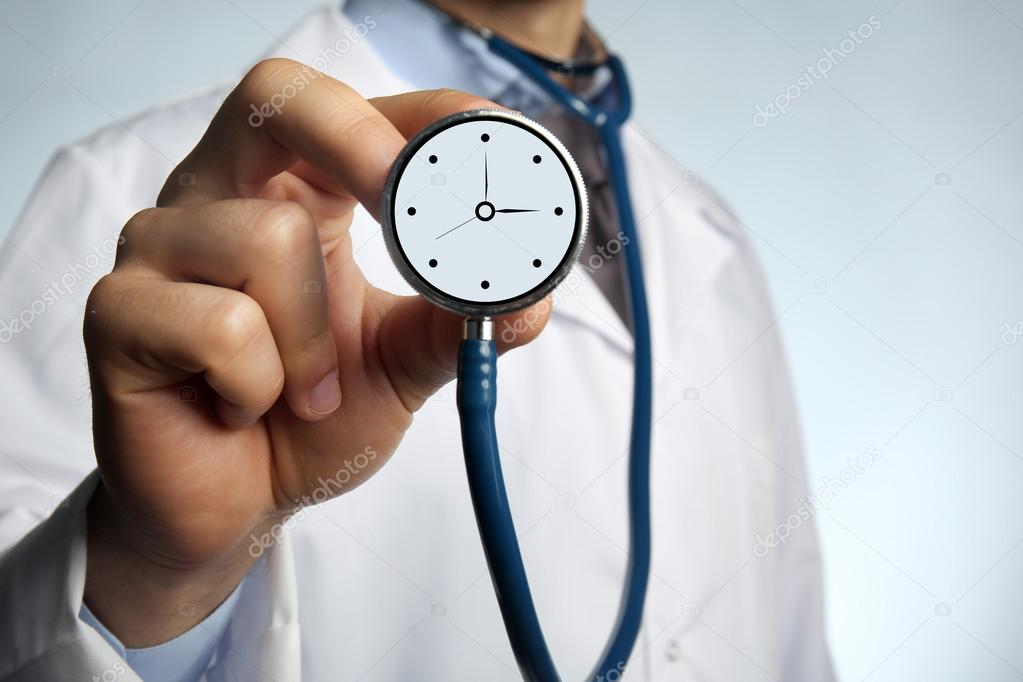 doctor holding stethoscope with clock stock photo belchonock