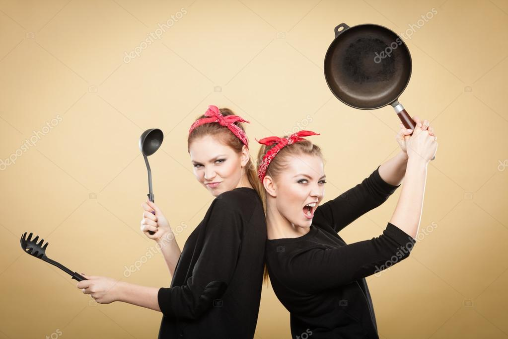 Retro styled women having fun with kitchen accessories.