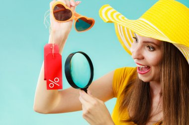 woman choosing glasses searching through magnifying glass