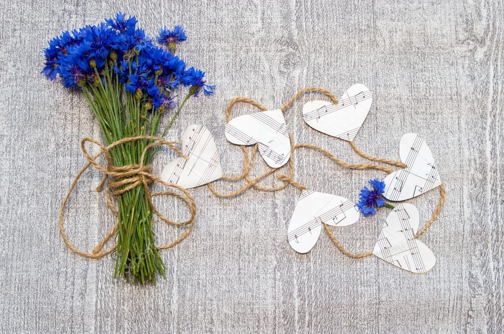 Bouquet of cornflowers with decorative hearts of music notes.