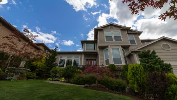 UHD časová prodleva pohybující mraky a modrá obloha nad předměstí realitní dům s udržovaný trávník a zahradu s japonského javoru stromů a keřů na částečně slunečný den