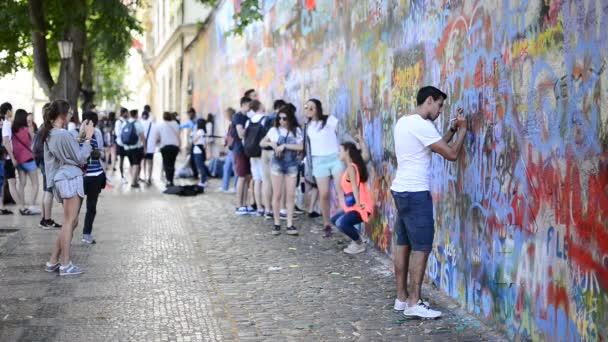 Mladý turista je podepisování na Lennonova zeď v Praze
