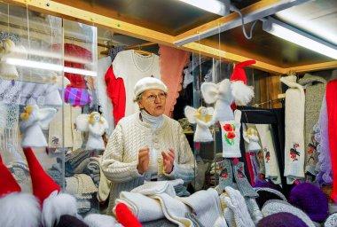 Woman selling festive warm clothes at Riga Christmas Market