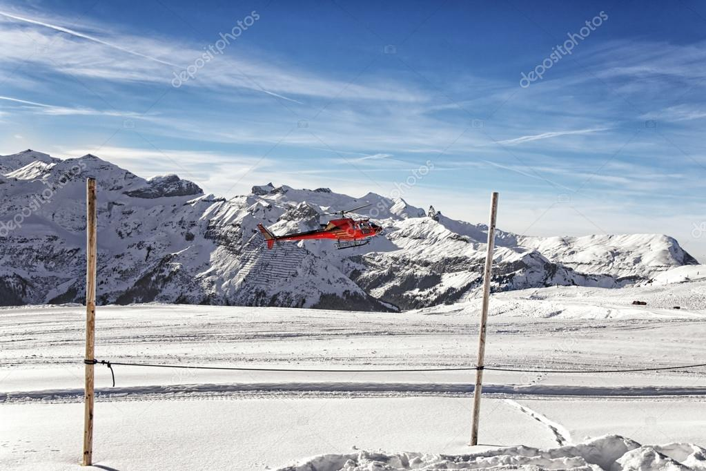 Landing of red helicopter at swiss alpine highland