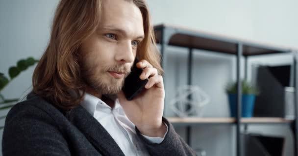 Nahaufnahme eines jungen, stylischen Büroleiters mit langen Haaren, der über Mobilkommunikation mit einem Kunden spricht, der Ratschläge gibt. Konzept des Ferndienstes.
