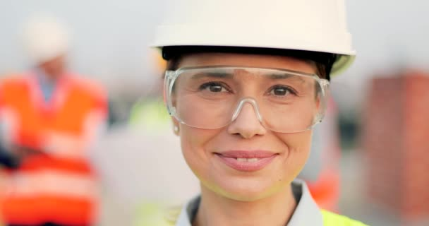Porträt einer schönen kaukasischen jungen Frau in Kaskade und Brille, die auf der Baustelle steht und in die Kamera lächelt. Bauarbeiterin in Brille beim Bauen. Unklarer Hintergrund.