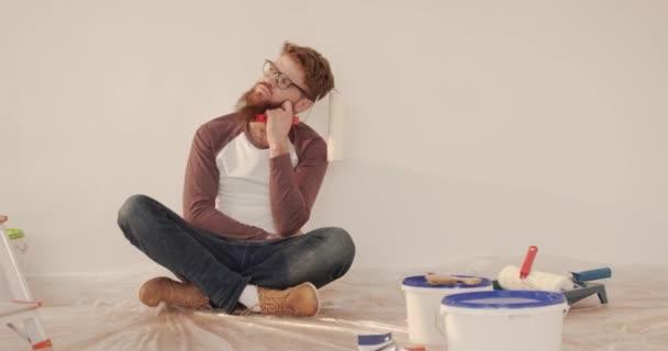 Junger gutaussehender kaukasischer Mann mit Bart und Brille sitzt mit überkreuzten Beinen auf dem Boden und hält einen Farbroller in der Hand.