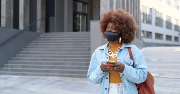 African American young stylish pretty hipster woman with curly hair wig and in mask walking at urban street and using smartphone. Beautiful female outdoor in city texting message on mobile phone.
