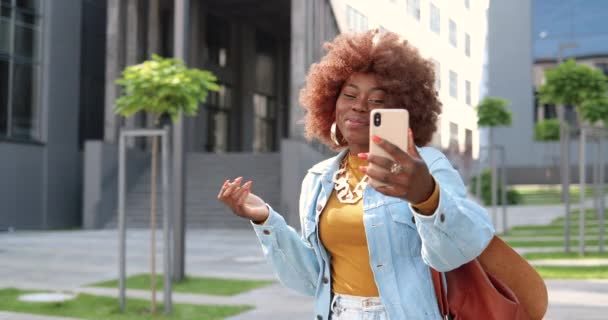 African American beautiful happy smiled woman talking via webcam on mobile phone outside. Cheerful stylish curly female videochatting on cellphone and smiling. Video call conversation. Videochat.