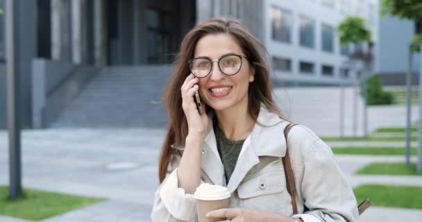 Kaukasische fröhliche junge stilvolle Frau, die morgens auf der Straße mit dem Handy telefoniert und ein Heißgetränk schlürft. Schöne glückliche Frau, die am Handy spricht und Kaffee trinkt. Draußen.