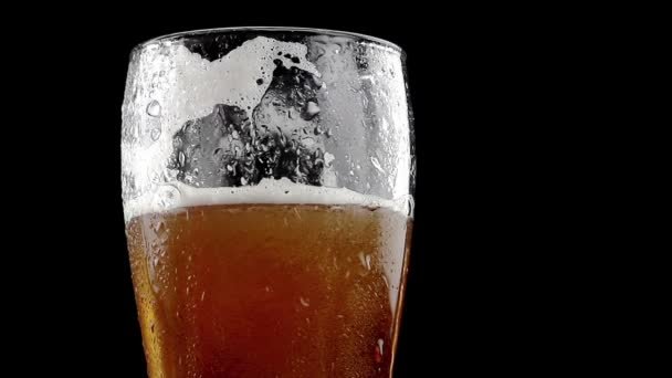 pivo s pěnou do skla na černém pozadí