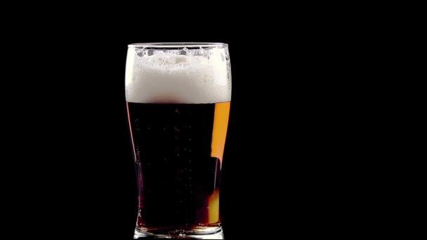 čerstvé pivo s pěnou do skla na černém pozadí