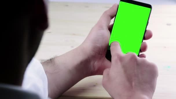 muž ručně pomocí chytrý telefon s chroma klíč na dřevěné tabulce za pohled, zelená obrazovka, životní styl komunikace s smartphone