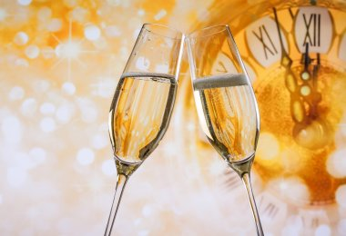 New Year or Christmas at midnight with champagne flutes make cheers, golden bokeh and clock