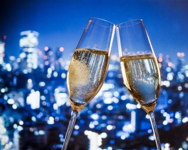 champagne flutes with golden bubbles on blue city night lights background