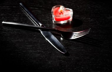 Valentine day table setting with knife, fork, red burning heart shaped candle