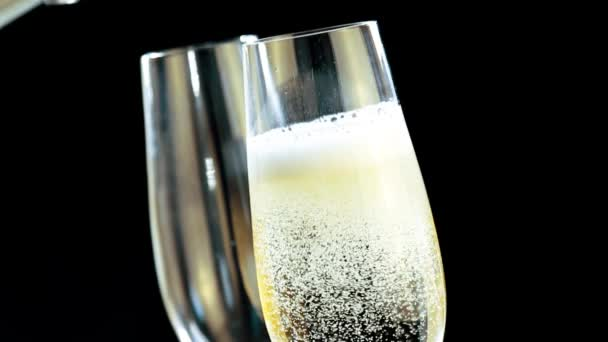 Champagne into flutes with golden bubbles on black background