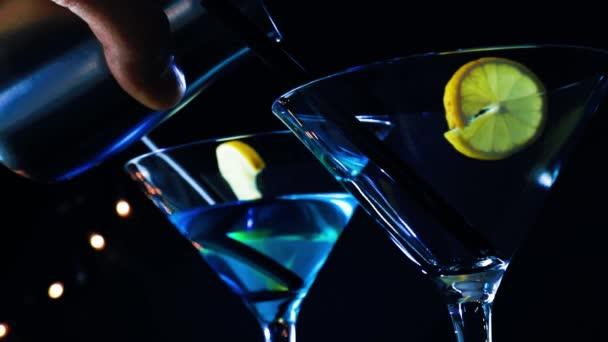 Barman, odlévání modré a žluté koktejlové nápoje na disco bar tabulka